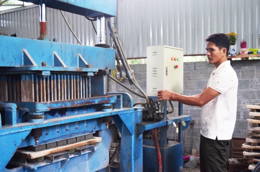Anh Vũ Tiến Cường vận hành máy sản xuất gạch không nung bán tự động. Ảnh: THÁI CƯỜNG