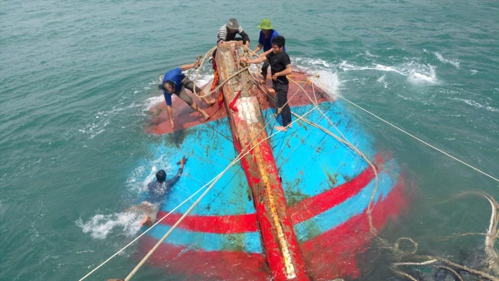 Ngư dân và lực lượng biên phòng đang trục vớt tàu QNg-97459TS. Ảnh: H.A