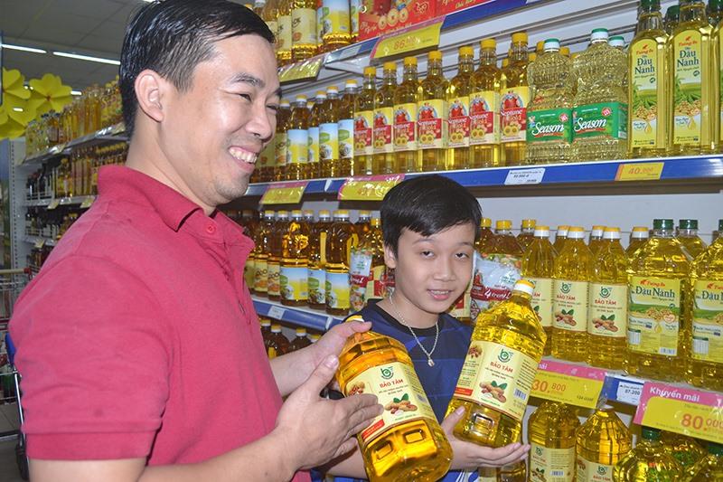 Sản xuất dầu thực vật nguyên chất của HTX Bảo Tâm (Tam Kỳ) có mặt ở siêu thị Co.opmart. Ảnh: VIỆT NGUYỄN