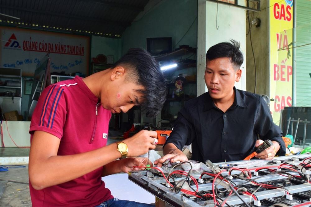 Anh Trần Ngọc Phúc (phải) hướng dẫn nhân viên lắp đặt bảng mạch đèn Led. Ảnh: THÁI CƯỜNG
