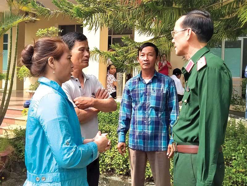 Thiếu tướng Nguyễn Đình Tiến trao đổi với các hộ tiểu thương bên ngoài cuộc đối thoại. Ảnh: N.Đ