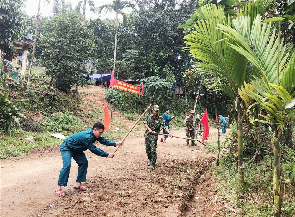 Cán bộ chiến sĩ Trung đoàn 143 giúp dân Thôn 2 xã Trà Đốc (Bắc Trà My) phát quang, dọn dẹp đường liên thôn. Ảnh: K.T