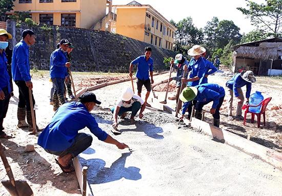 Hướng về cộng đồng bằng những phần việc ý nghĩa đã trở thành mục tiêu của Huyện đoàn Nam Giang. TRONG ẢNH: Đoàn viên thanh niên giúp dân làm đường bê tông nông thôn. Ảnh: Đ.N