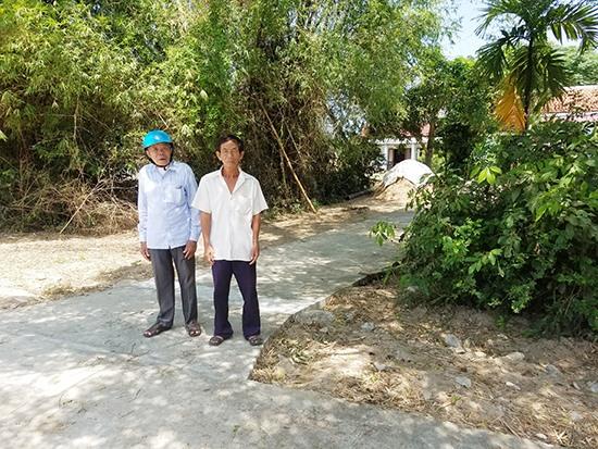 Ông Trương Công Hiếu (trái) và con trai bà Chức đứng trên lối đi bằng bê tông mà hàng xóm xây dựng trái phép xuyên qua thửa đất của gia đình. Ảnh: H.S