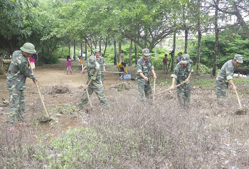 Ban CHQS huyện Lý Sơn giúp Trường Tiểu học xã An Vĩnh dọn vệ sinh môi trường. Ảnh: Đ.N