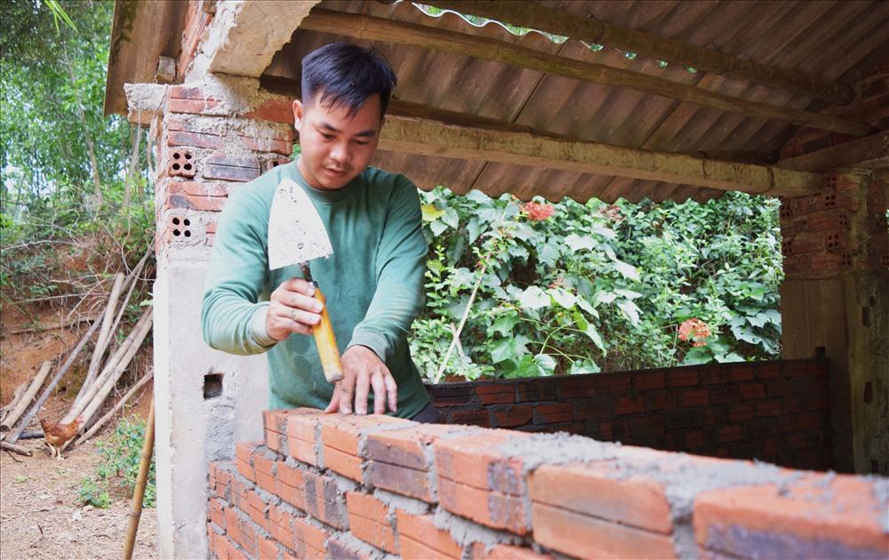 Anh Trạng tự tay xây dựng chuồng bò để chuẩn bị cho dự án chăn nuôi mới. Ảnh: THÁI CƯỜNG