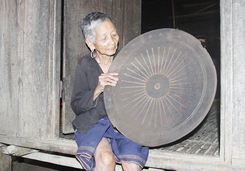 Cụ bà Bhơnướch Thị Bhươi (95 tuổi, vợ ông Bhơriu Bhang) bên cái khiêng được chồng giao giữ gìn như vật báu của tộc họ Bhơriu. Ảnh: BHƠRIU QUÂN