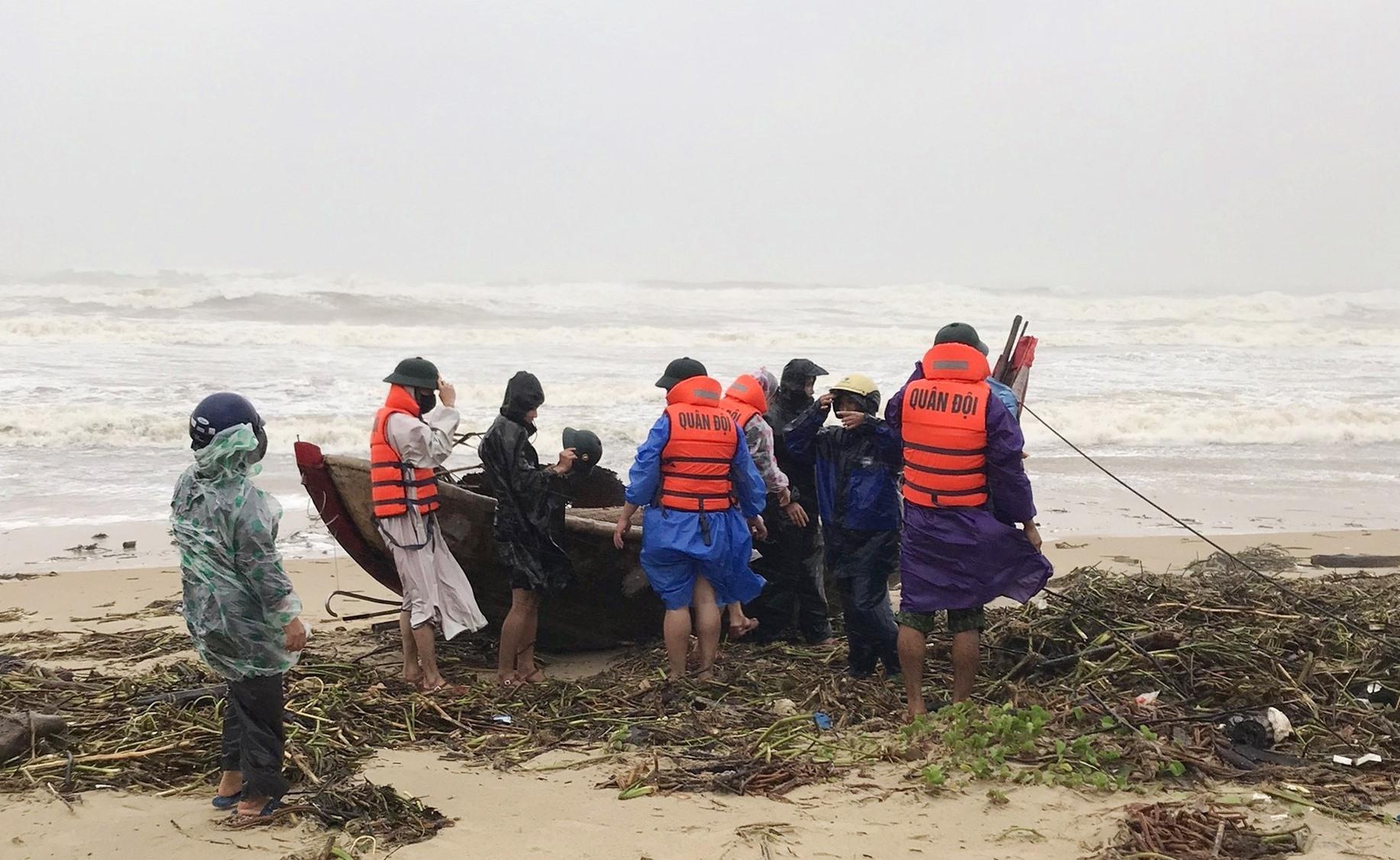 Bộ đội biên phòng giúp nhân dân kéo tàu vào bờ tránh bão. Ảnh: H.A