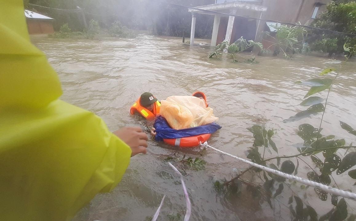 Một cháu bé được hai chiến sĩ đưa ra khỏi vùng ngập sâu. (Ảnh do Phòng Cảnh sát đường thủy cung cấp)