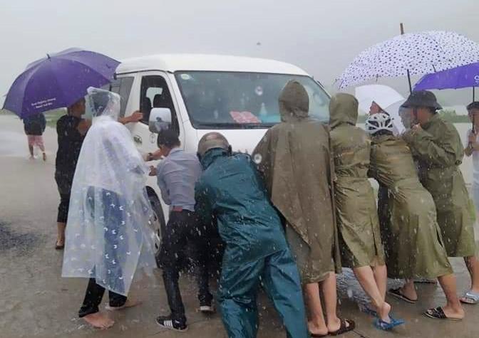 Ứng cứu người dân khi lưu thông qua đoạn đường nước chảy xiết. Ảnh: Tuyết Trương