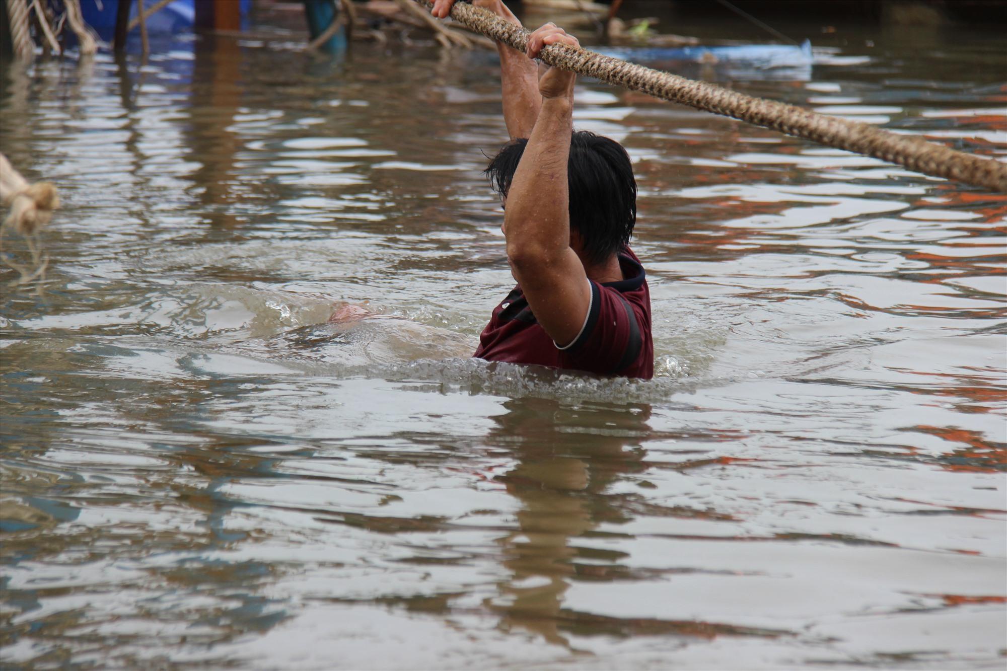 Nước sâu chảy xiết nên thợ lặn phải đu dây từ bờ ra thuyền đang bị chìm. Ảnh: HOÀI AN