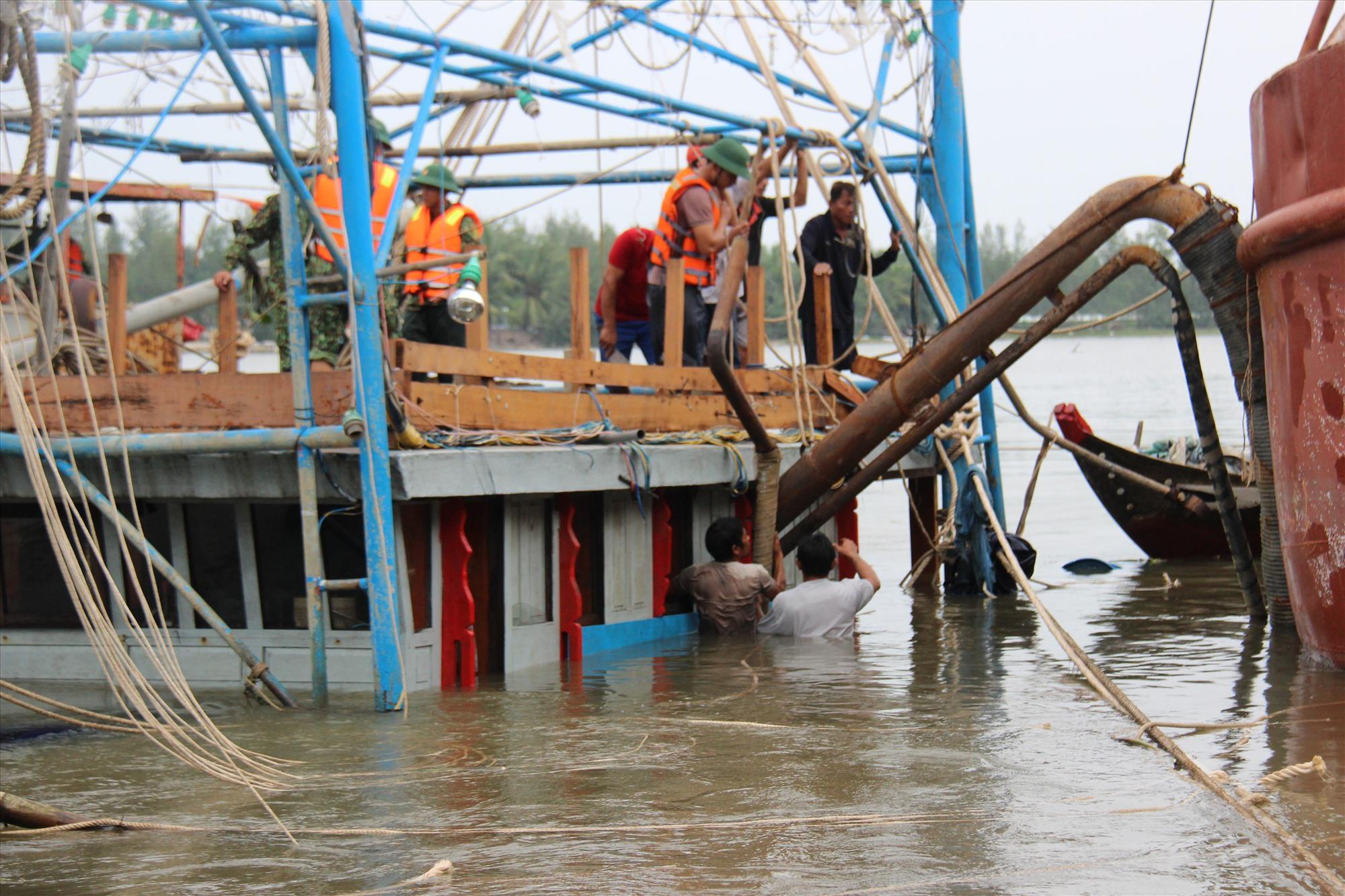 Hút bùn đất trong khoang tàu để tìm kiếm hai người mất tích. Ảnh: HOÀI AN