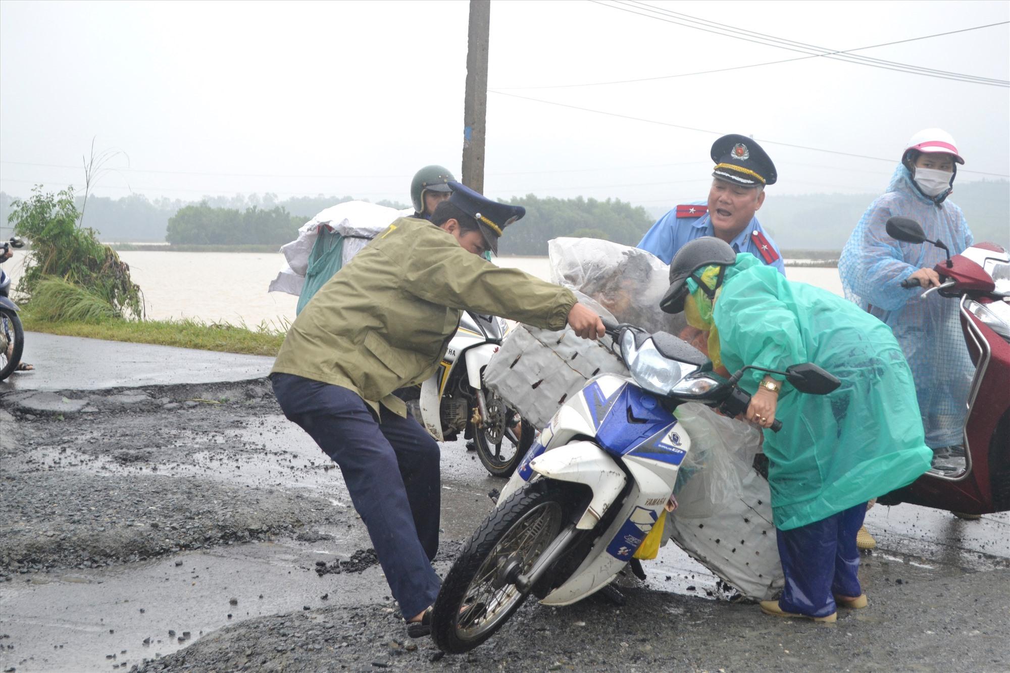 Thanh tra viên Thanh tra Sở GTVT giúp người dân bị té ngã xe phía tây cầu Đại Hiệp. Ảnh: CT