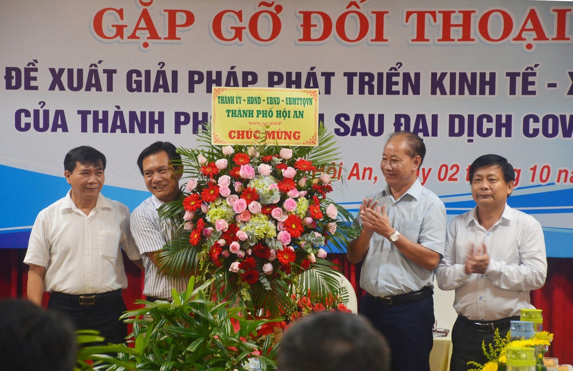 Lãnh đạo TP.Hội An tặng hoa chúc mừng cộng đồng doanh nghiệp Nhân ngày Doanh nhân Việt Nam. Ảnh: Q.T