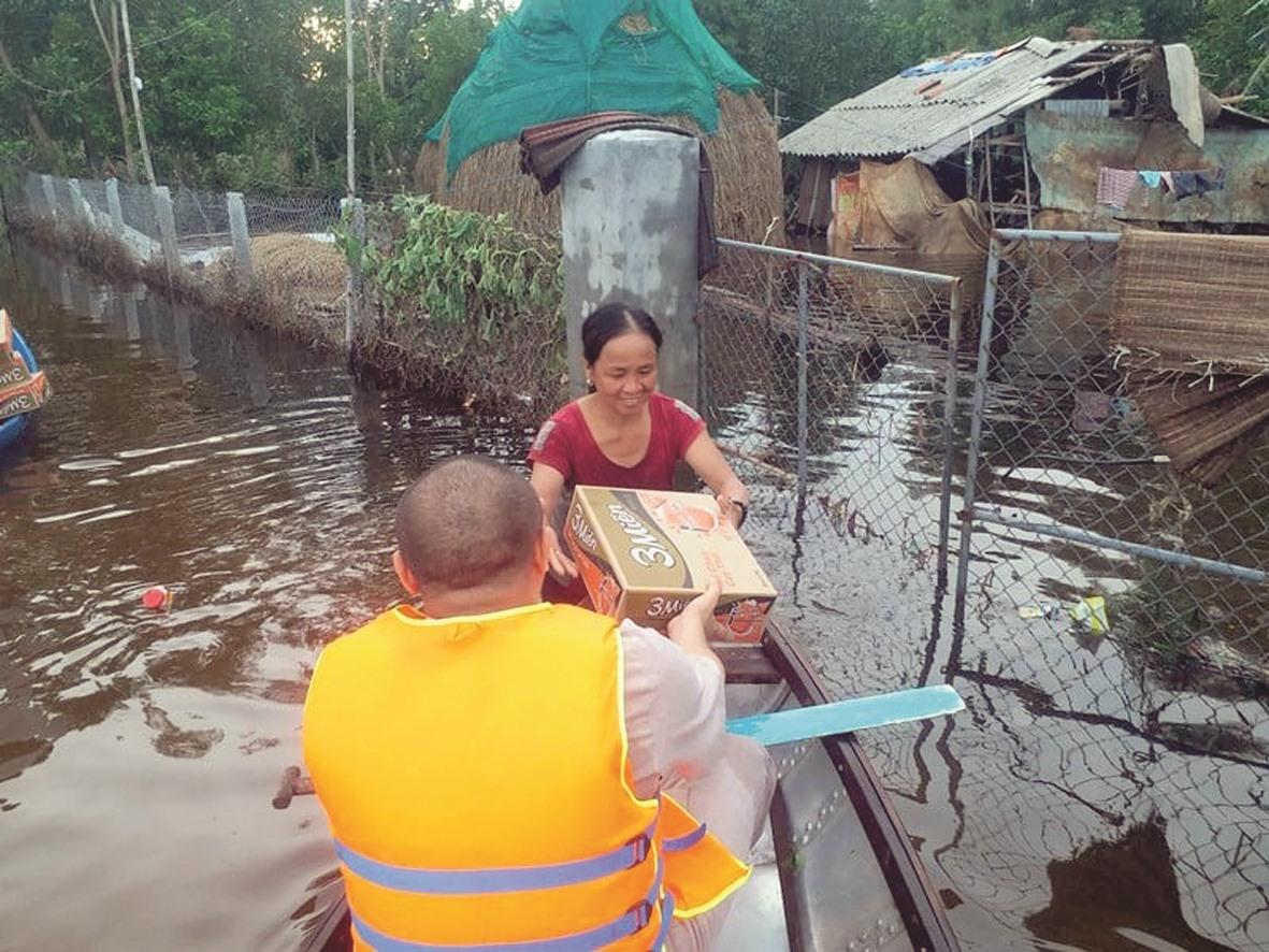 Chèo ghe đến những nơi ngập lụt để hỗ trợ mì tôm cho người dân.