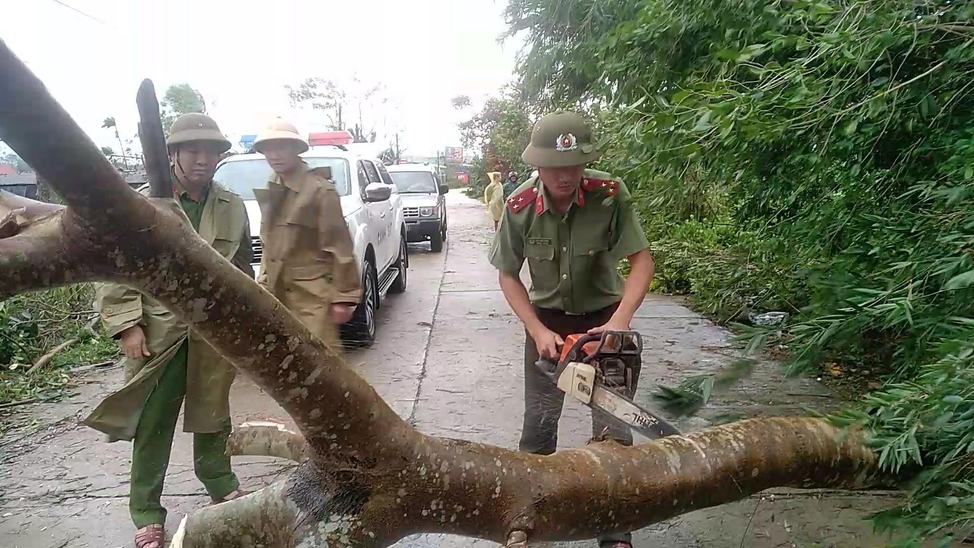 Lực lượng Công an Thăng Bình giúp người dân cưa cây, thông tuyến giao thông tại xã Bình Quý. Ảnh: M.TÂN