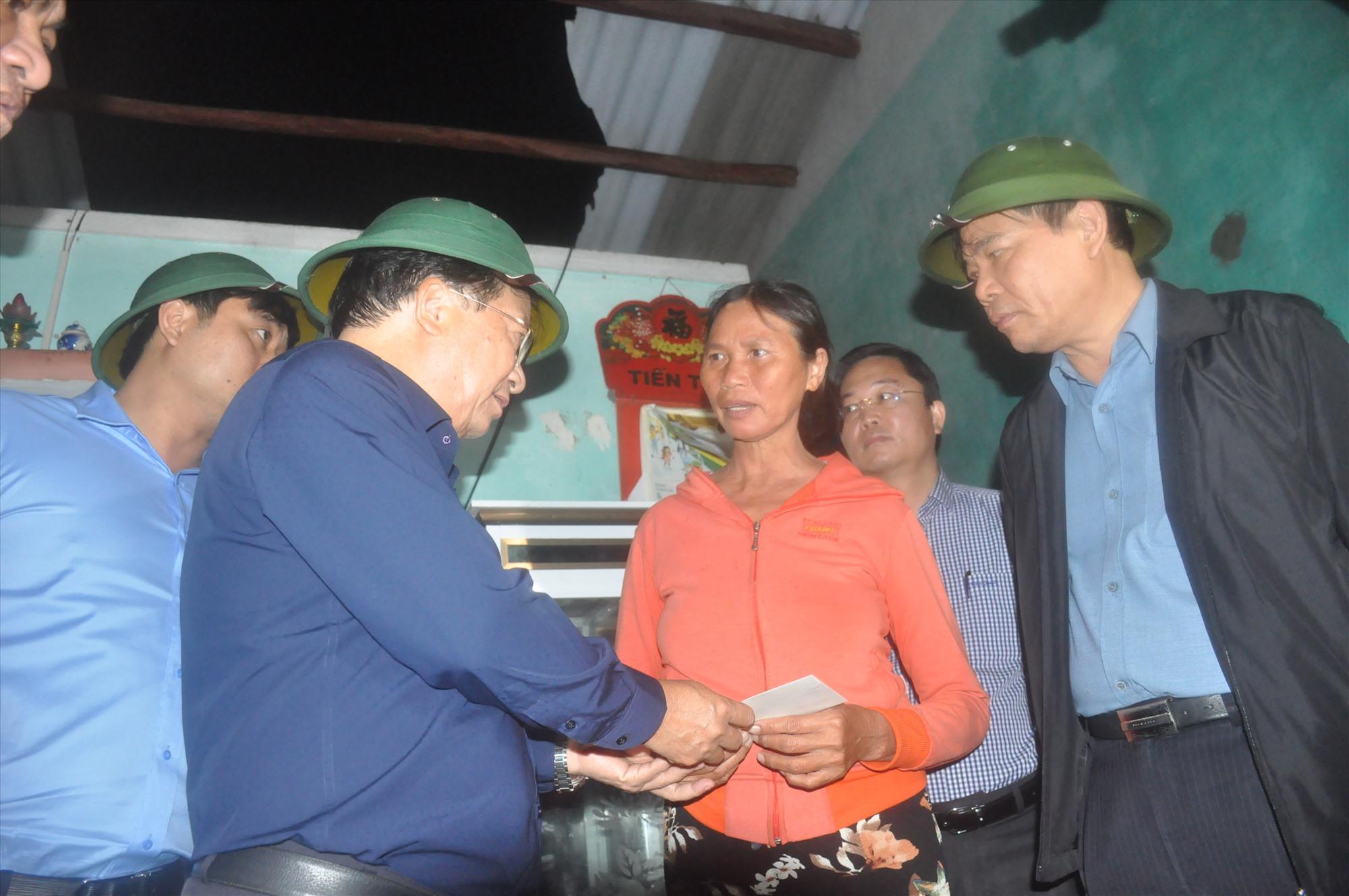 Phó Thủ tướng Trịnh Đình Dũng tặng quà hỗ trợ cho một hộ dân ở xã Bình Minh có nhà bị tốc mái do bão. Ảnh: N.Đ