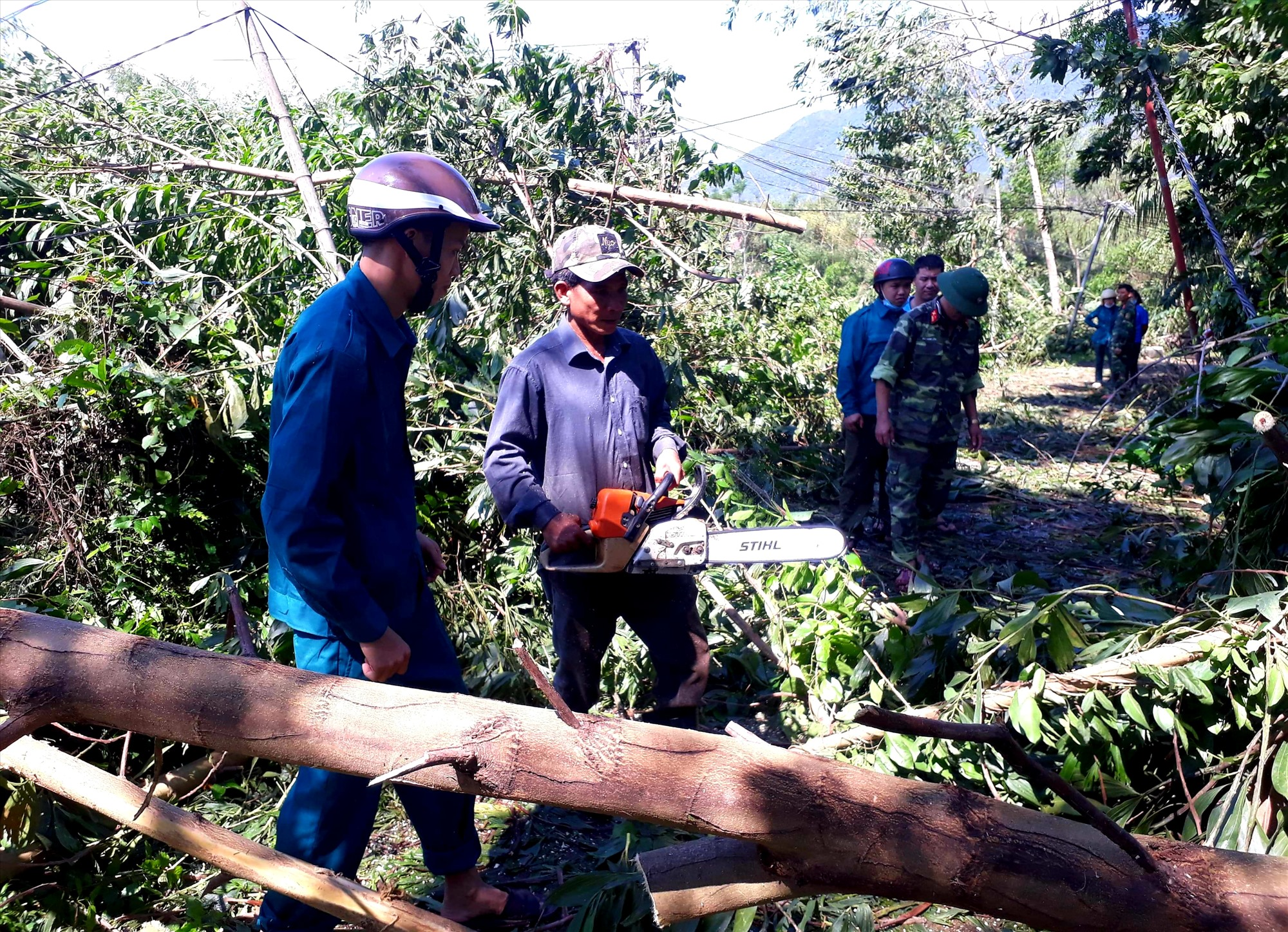 Nhiều lực lượng của huyện Quế Sơn khẩn trương xử lý cây cối ngã đổ trên các tuyến đường. Ảnh: S.T
