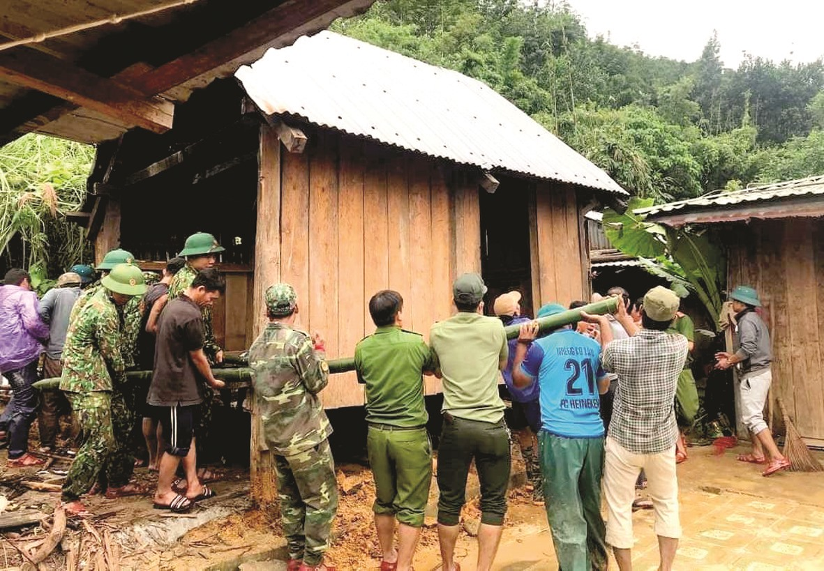Lực lượng cứu hộ và bà con huyện Tây Giang di dời ngôi nhà khỏi vùng nguy hiểm. Ảnh: Đ.N