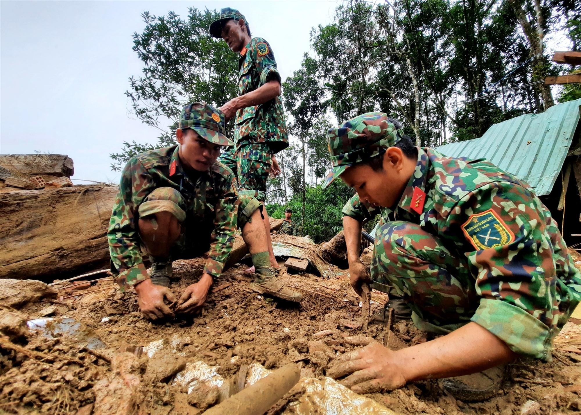 Các chiến sĩ dùng tay bươi nhẹ nơi thi thể nạn nhân được phát hiện. Ảnh: P.V