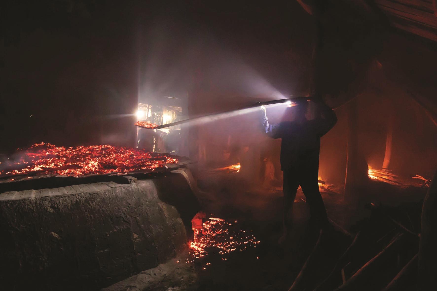 Để có nhiệt lượng đều từ dưới lên trên, người thợ lấy than phủ một lớp trên miệng lò tạo đều nhiệt cho mẻ muối.