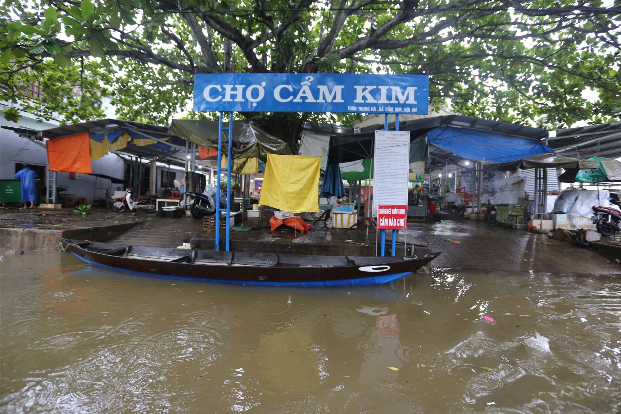 Sáng 8/10, chợ Cẩm Kim, TP Hội An nằm ven sông Thu Bồn bị nước lũ bủa vây nên ngừng hoạt động, tiểu thương đưa hàng lên cao hoặc đưa về nhà tránh lũ.