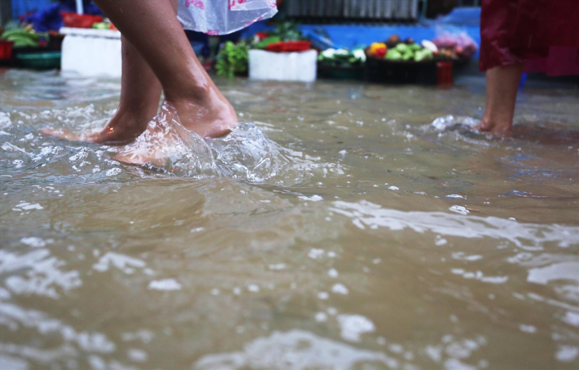 Để mua hàng, người dân xắn quần lên cao và lội nước để mua.
