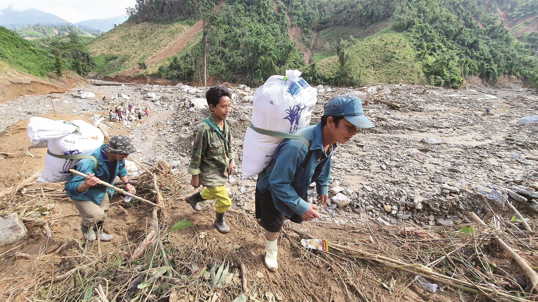 Hàng chục dân quân xã Phước Thành được huy động để gùi cõng lương thực, thực phẩm cho bà con vùng cô lập.