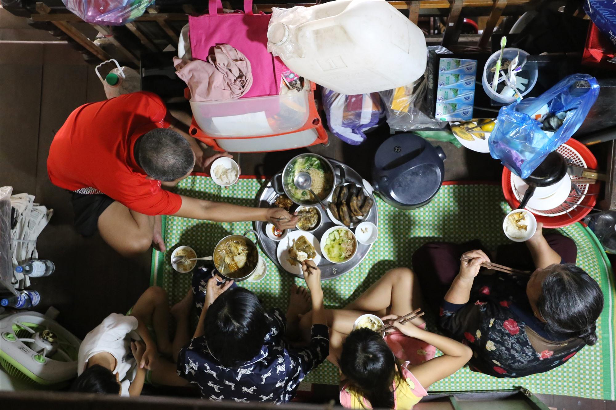 Sau khi nấu xong, gia đình Tiến có năm người, gồm hai vợ chồng, hai người con và mẹ già. Họ dọn ra ở hành lang ở gác lững ngồi ăn, xung quanh đồ đặc được lên cao tránh lũ.