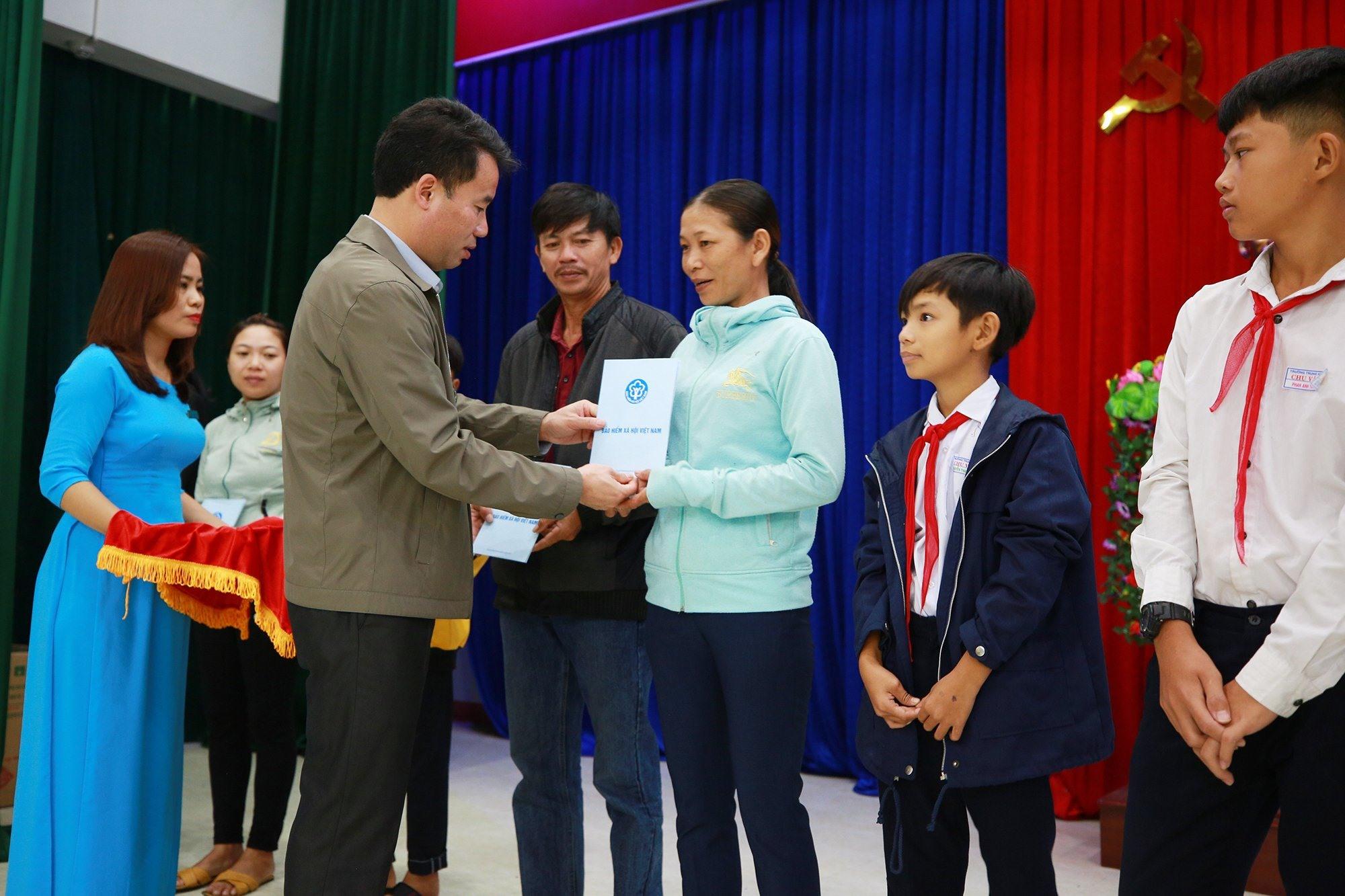 Tổng Giám đốc BHXH Việt Nam Nguyễn Thế Mạnh tặng thẻ BHYT cho người dân khó khăn tại Quảng Nam. Ảnh: D.L