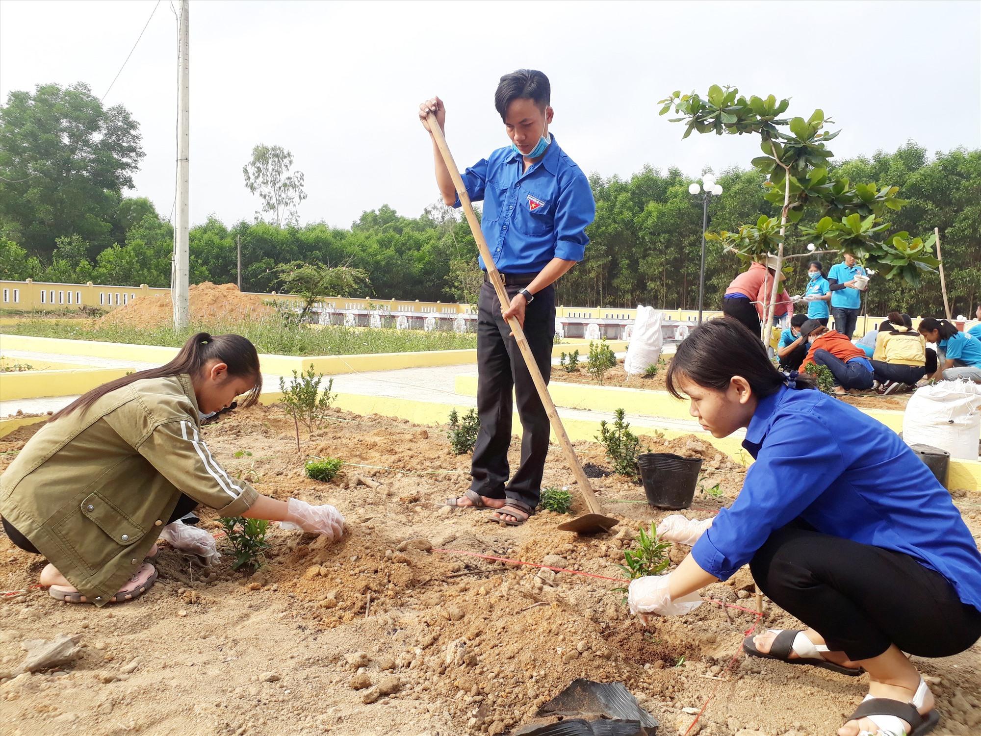 Đoàn viên thanh niên Quế Sơn trồng cây xanh tại Nghĩa trang liệt sĩ xã Quế An. Ảnh: T.P