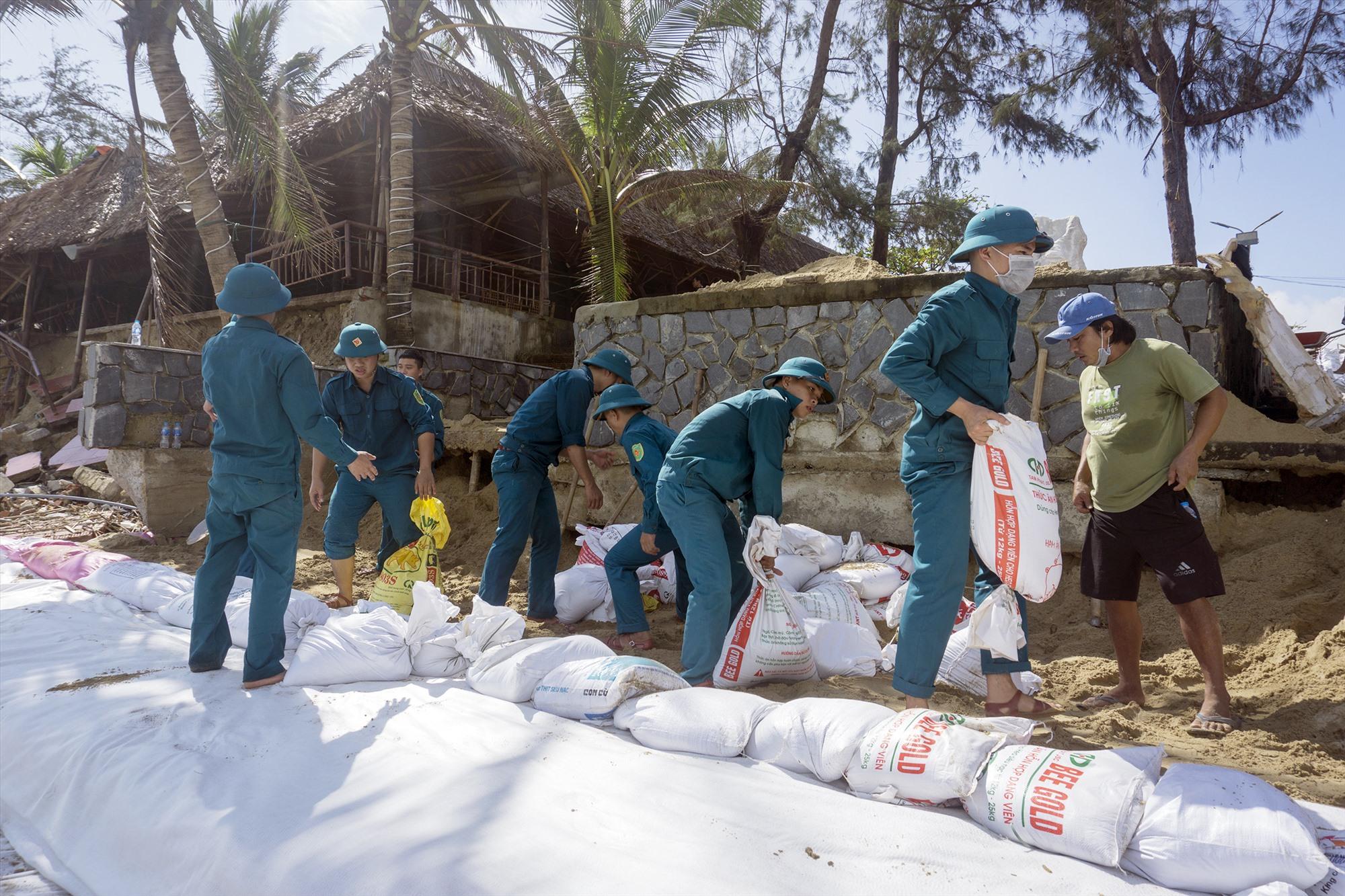 Lực lượng dân quân tự vệ chuyển những bao cát được vào sẵn.