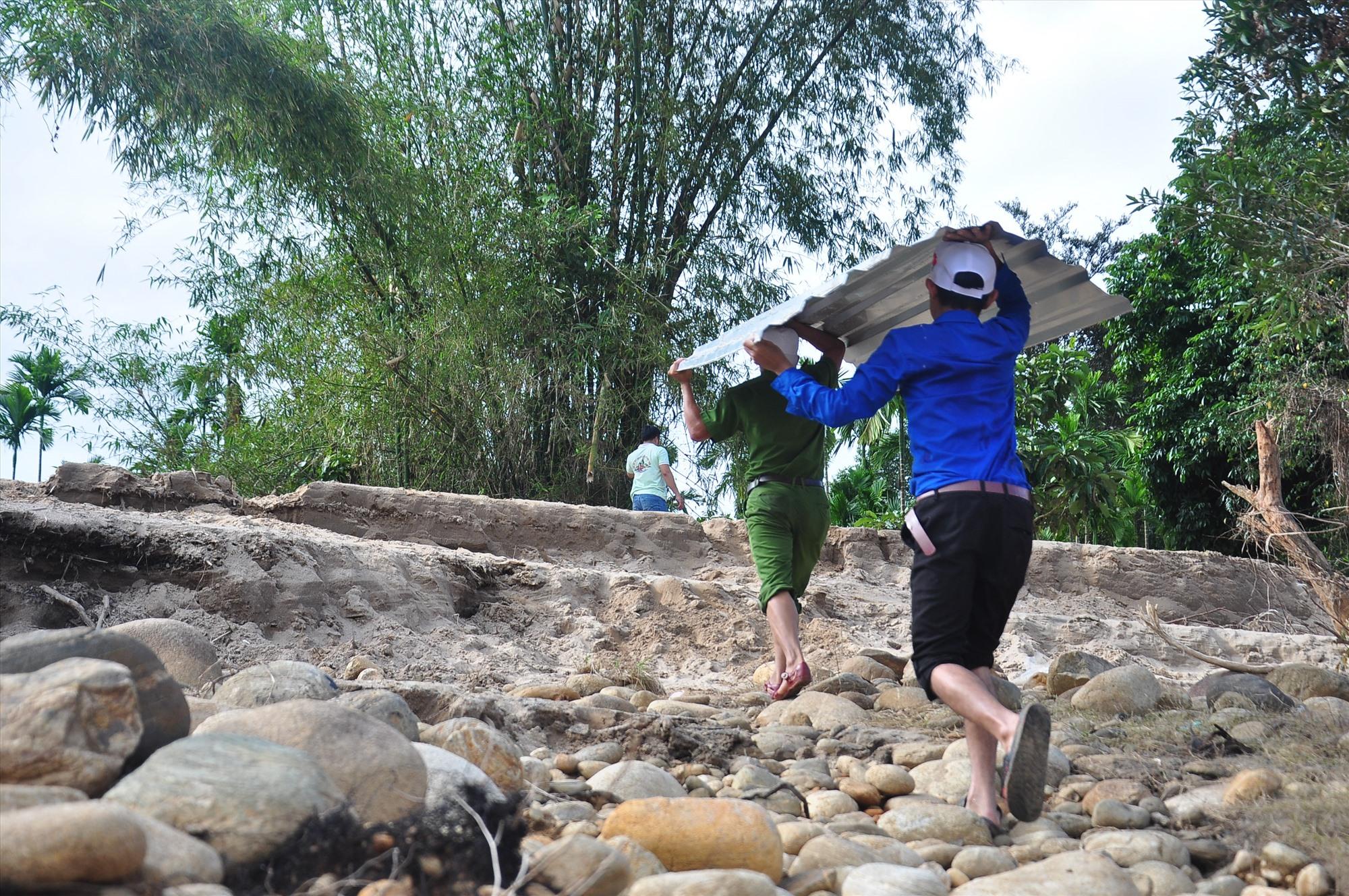 Thanh niên tình nguyện vận chuyển tôn từ bến sông vào làng Tắk Rối. Ảnh: VINH ANH