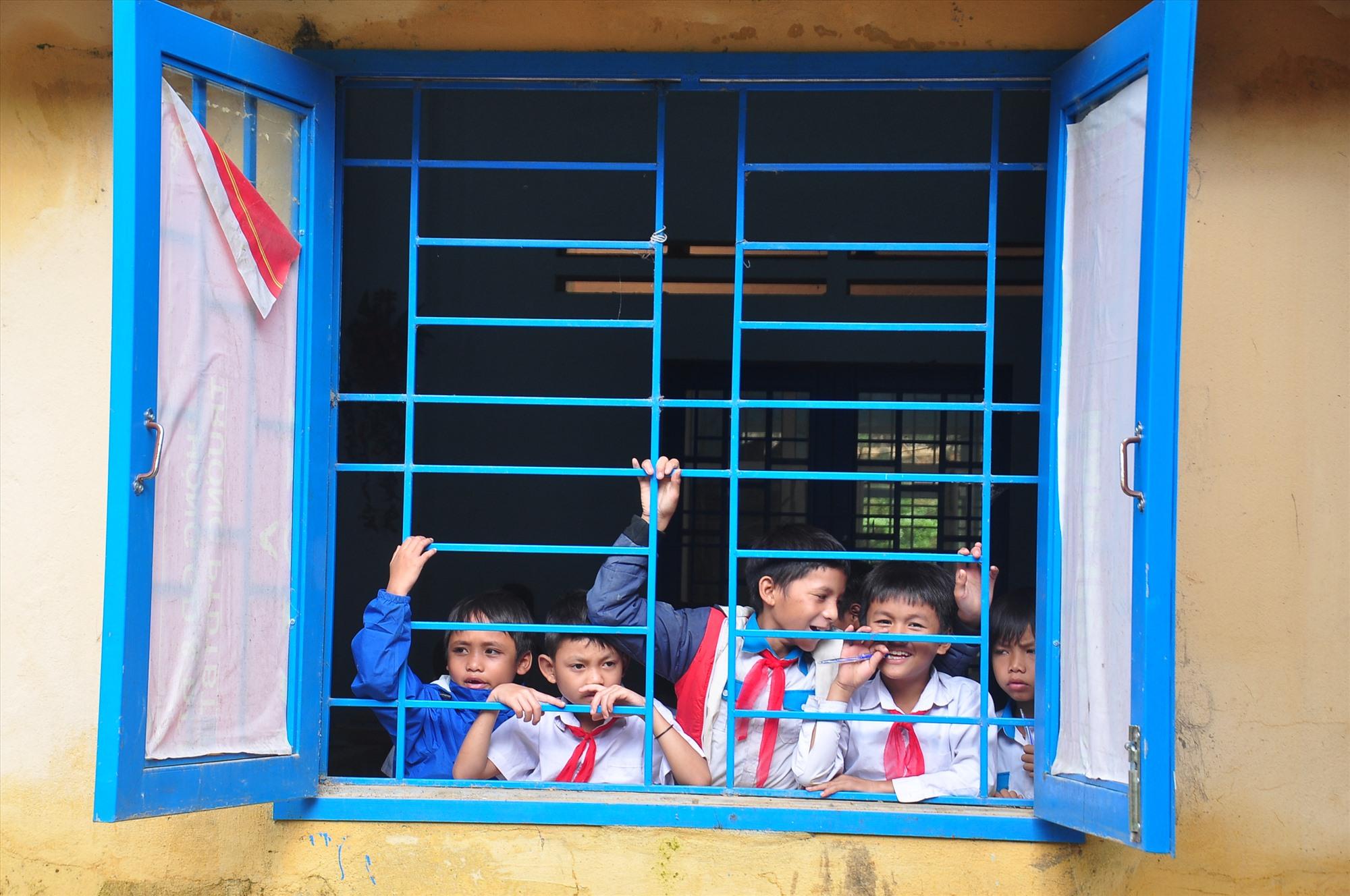Trong khi đó, phía bên trong nhà trường, các em học sinh vui vẻ theo dõi hoạt động của lực lượng tình nguyện trong giờ nghỉ. Ảnh: VINH ANH