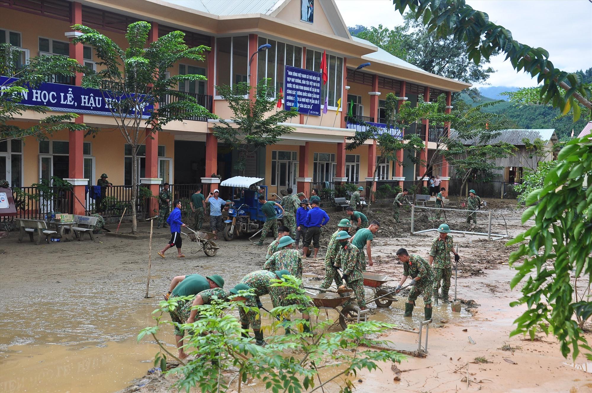 Cán bộ, chiến sĩ và thanh niên tình nguyện tổ chức dọn bùn đất trong sân trường. Ảnh: VINH ANH