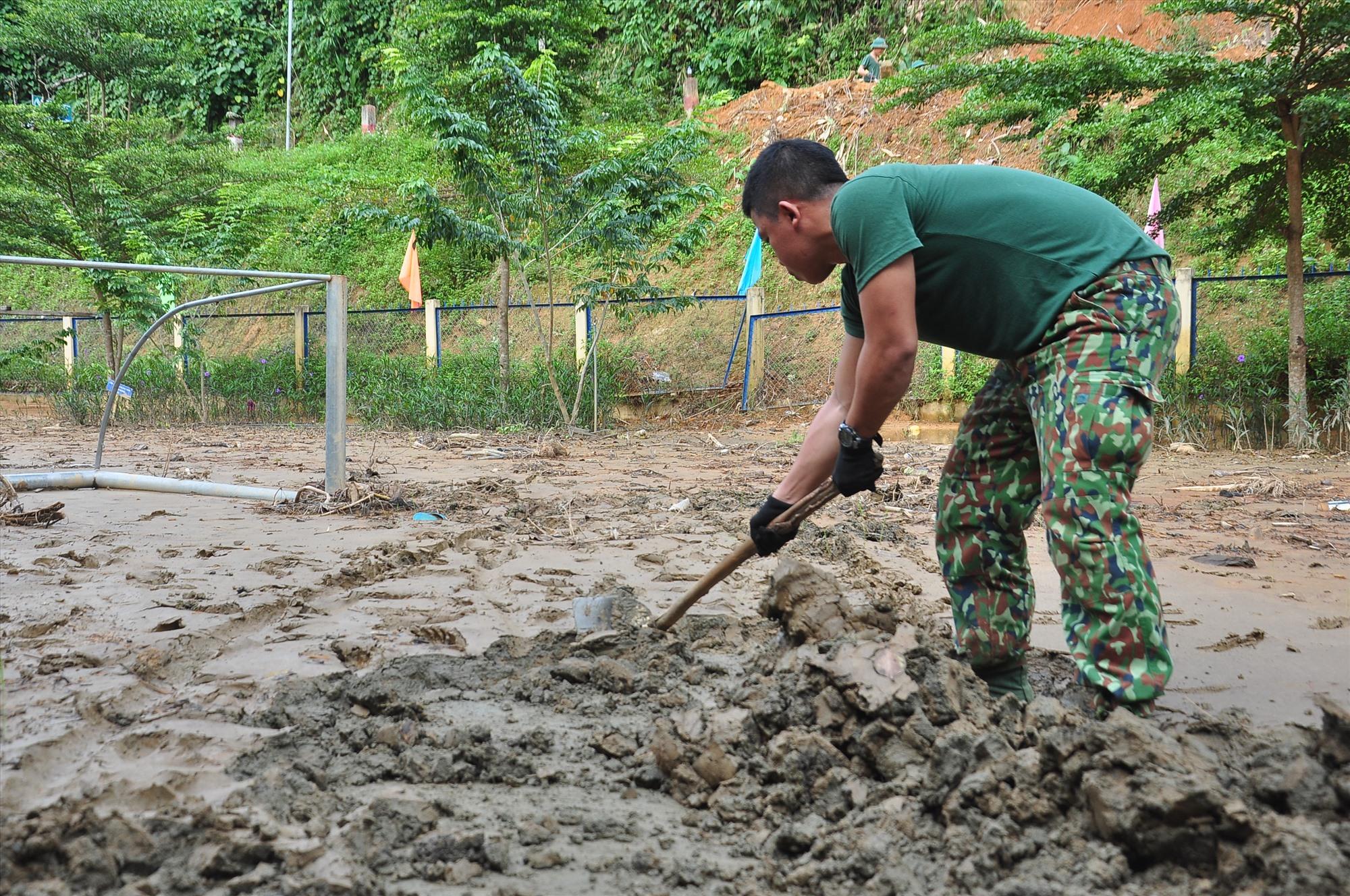 Một chiến sĩ đang cố gắng cào lớp bùn đất dày đặc, dính chặt trên sân trường. Ảnh: VINH ANH