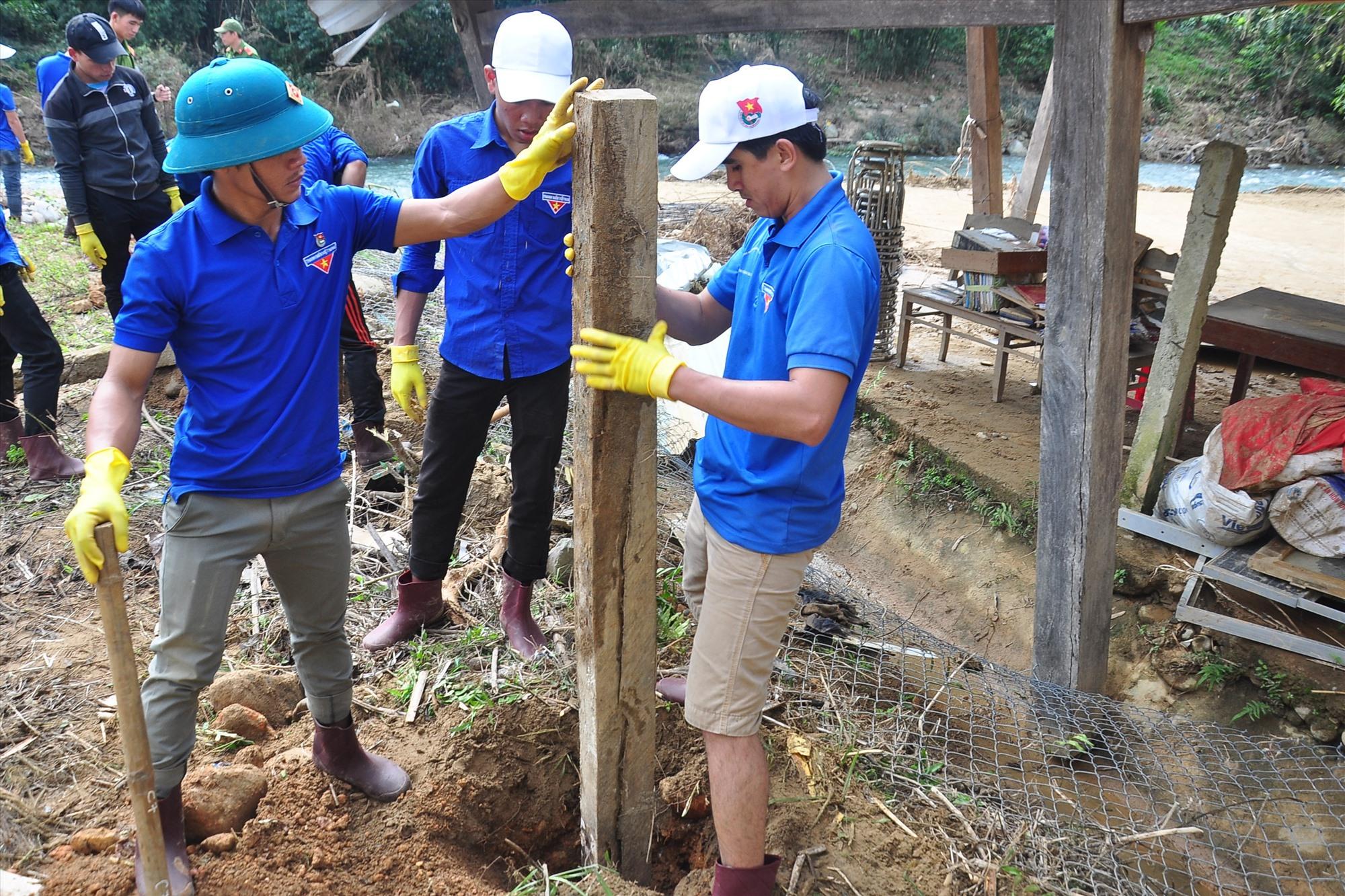 Đoàn thanh niên tình nguyện tiến hành chôn các trụ cọc để sửa chữa lại tường rào phía sau nhà trường. Ảnh: VINH ANH
