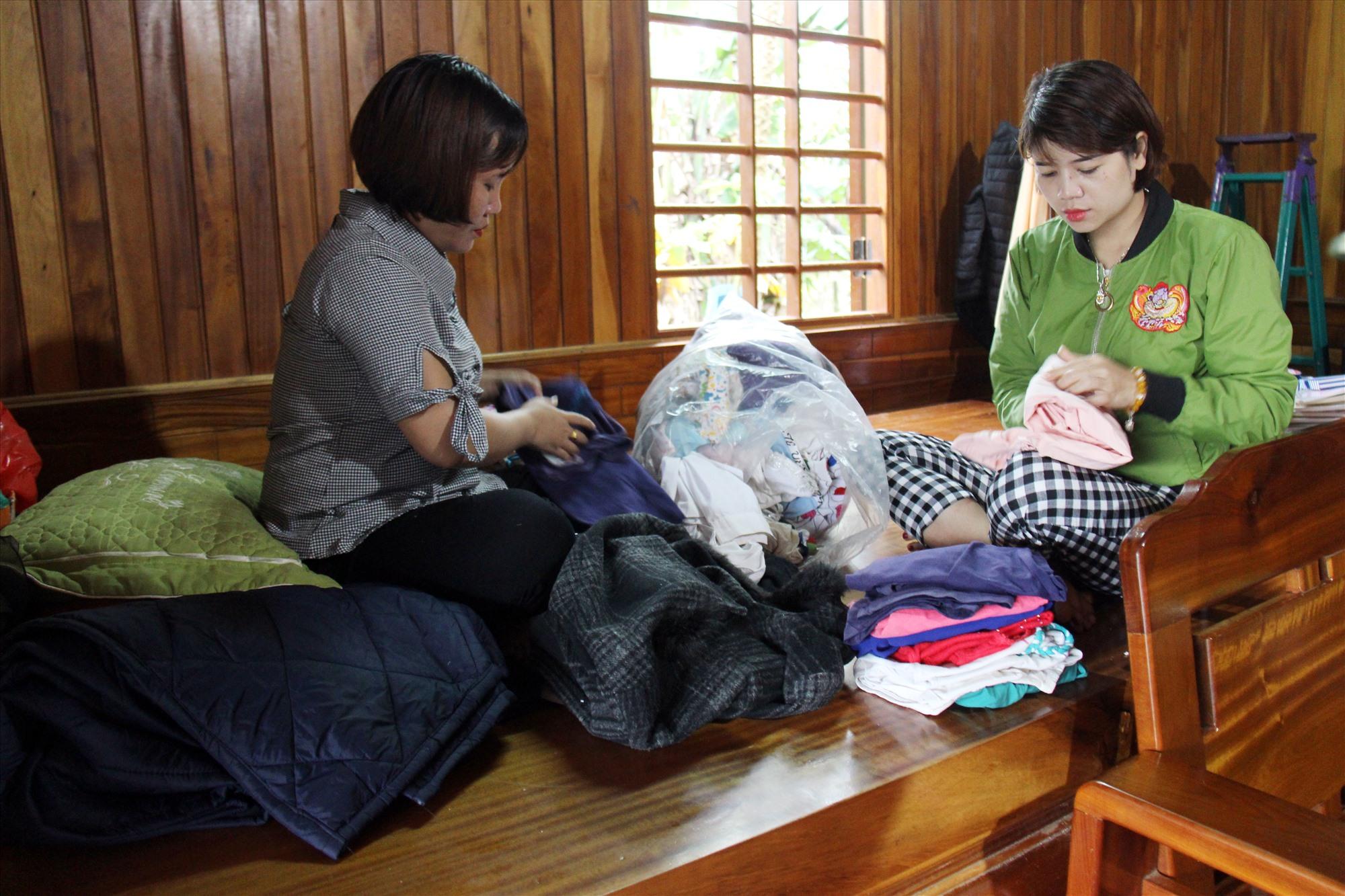 Cô Hà và cô Đêm sắp xếp lại mớ quần áo để chuyển vào cho bà con xã Phước Thành. Ảnh: T.C