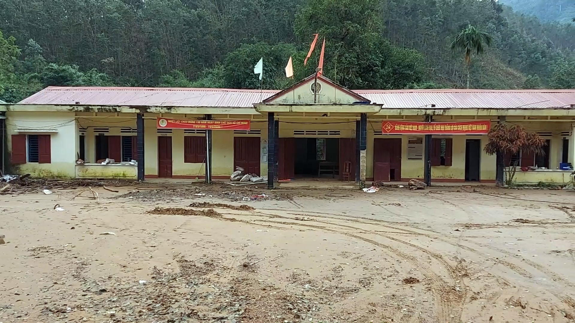 Bùn đất vẫn còn lấp kín sân trụ sở UBND xã Trà Leng. Ảnh: VĂN THỌ