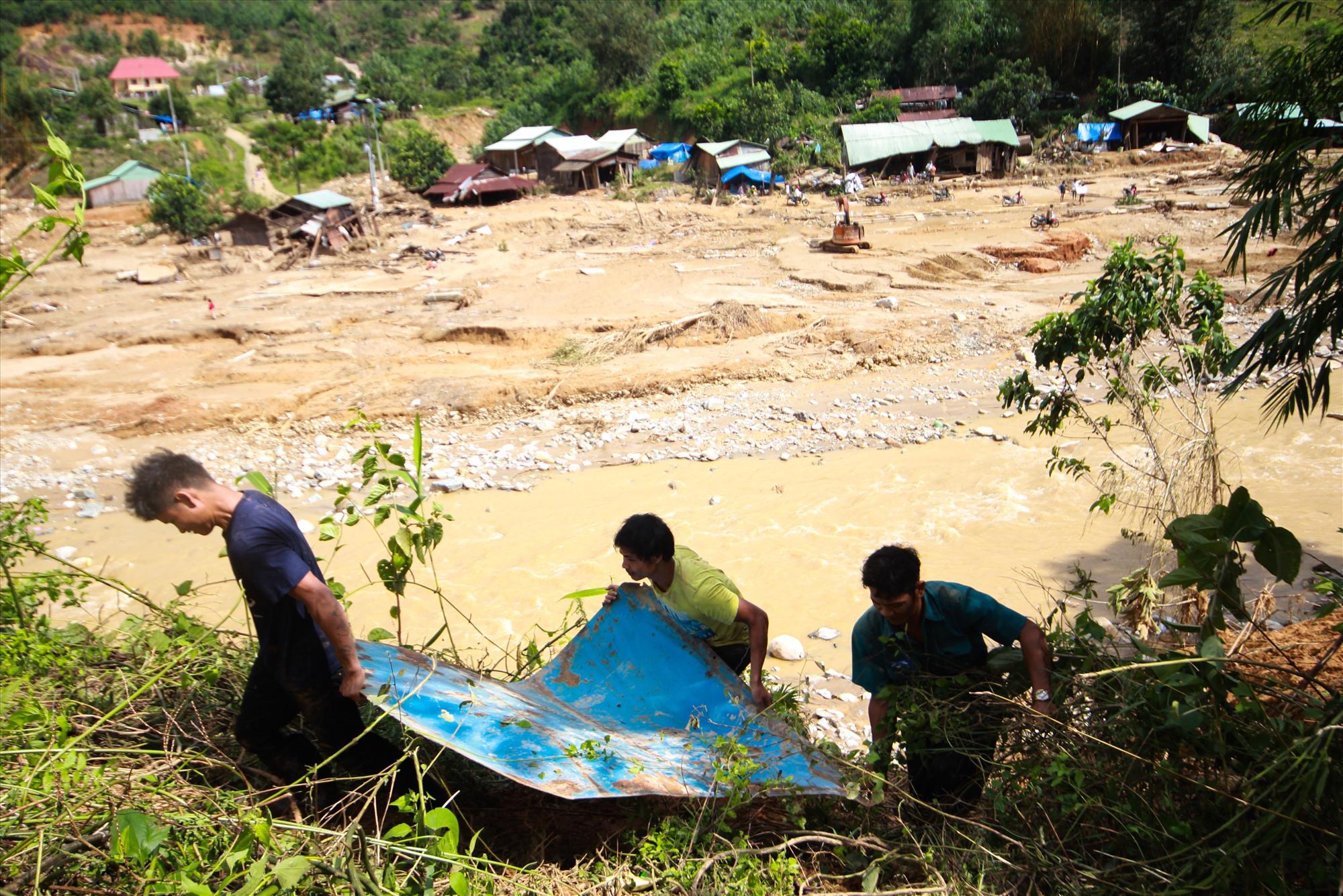 Người dân nhặt lại tấm thép bị lũ cuốn xuống dòng sông sau lũ. Ảnh: T.C