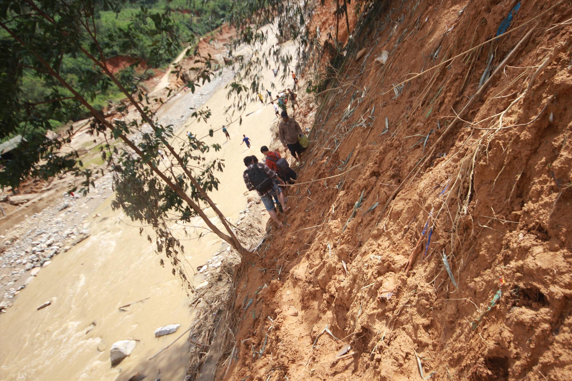 Đường vào thôn bị cô lập, người dân phải men theo sườn dốc, lội qua sông để về làng. Ảnh: T.C