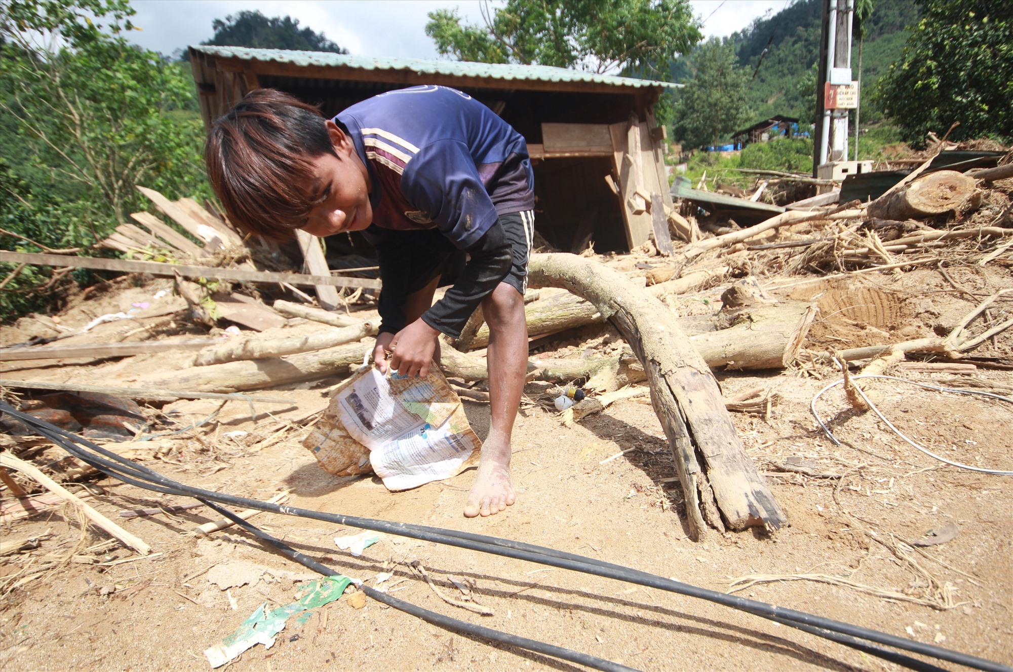 Em Hồ Văn Thoại nhặt nhạnh lại những quyển sách đã bị lấm lem bùn đất, ướt nhoẹt sau lũ. Ảnh: T.C