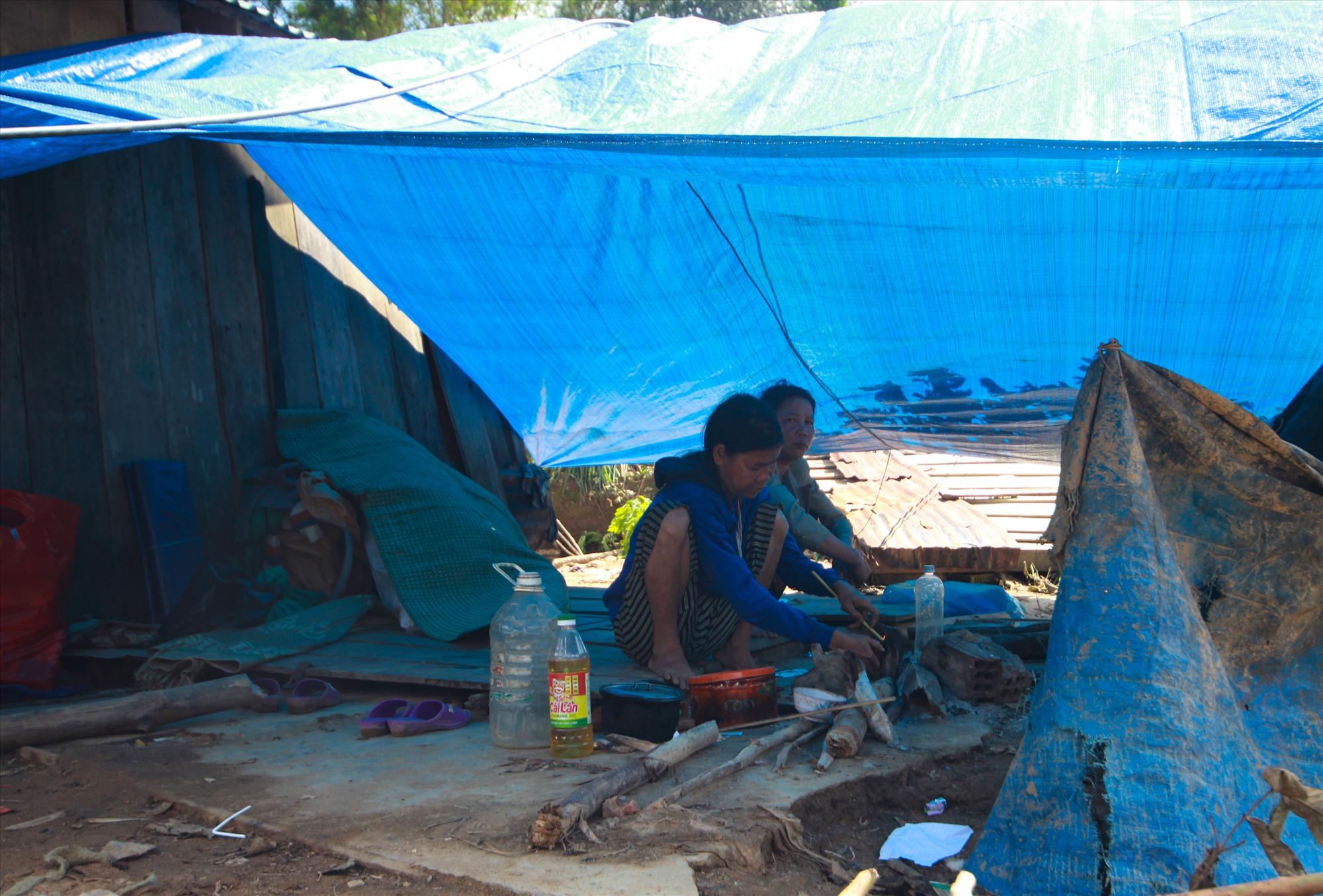 Người dân dựng lều bạt tạm làm nơi nấu ăn. Các hộ này phải ngủ nhờ trong nhà làng. Ảnh: T.C