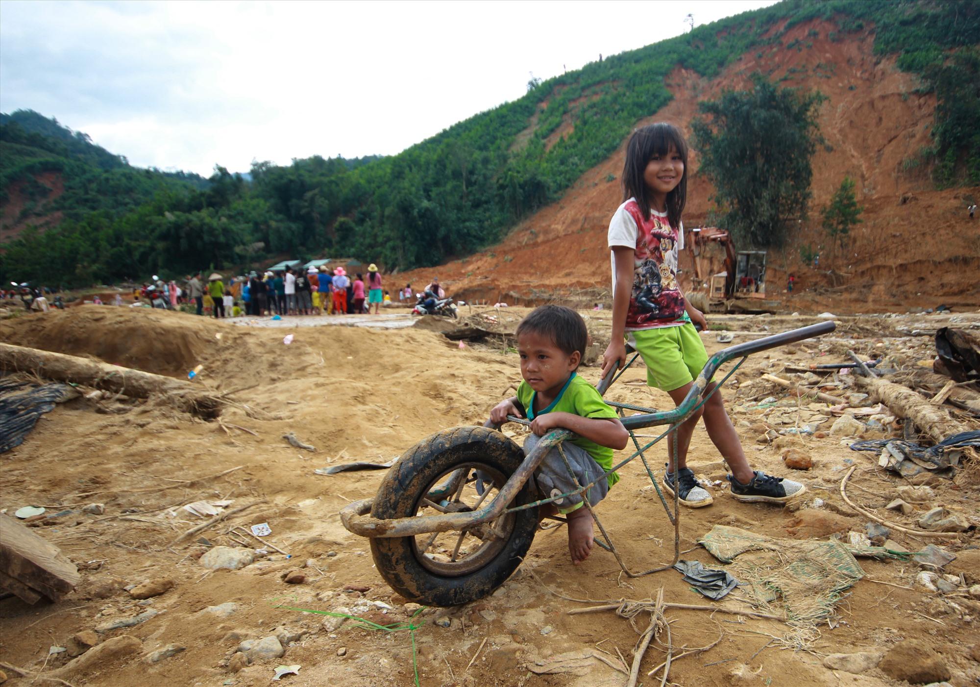 Hai em nhỏ thôn Trà Văn A lấy chiếc xe đẩy làm đồ chơi. Chiếc xe đẩy này bị hỏng sau khi được lôi ra từ đống bùn đất. Ảnh: T.C