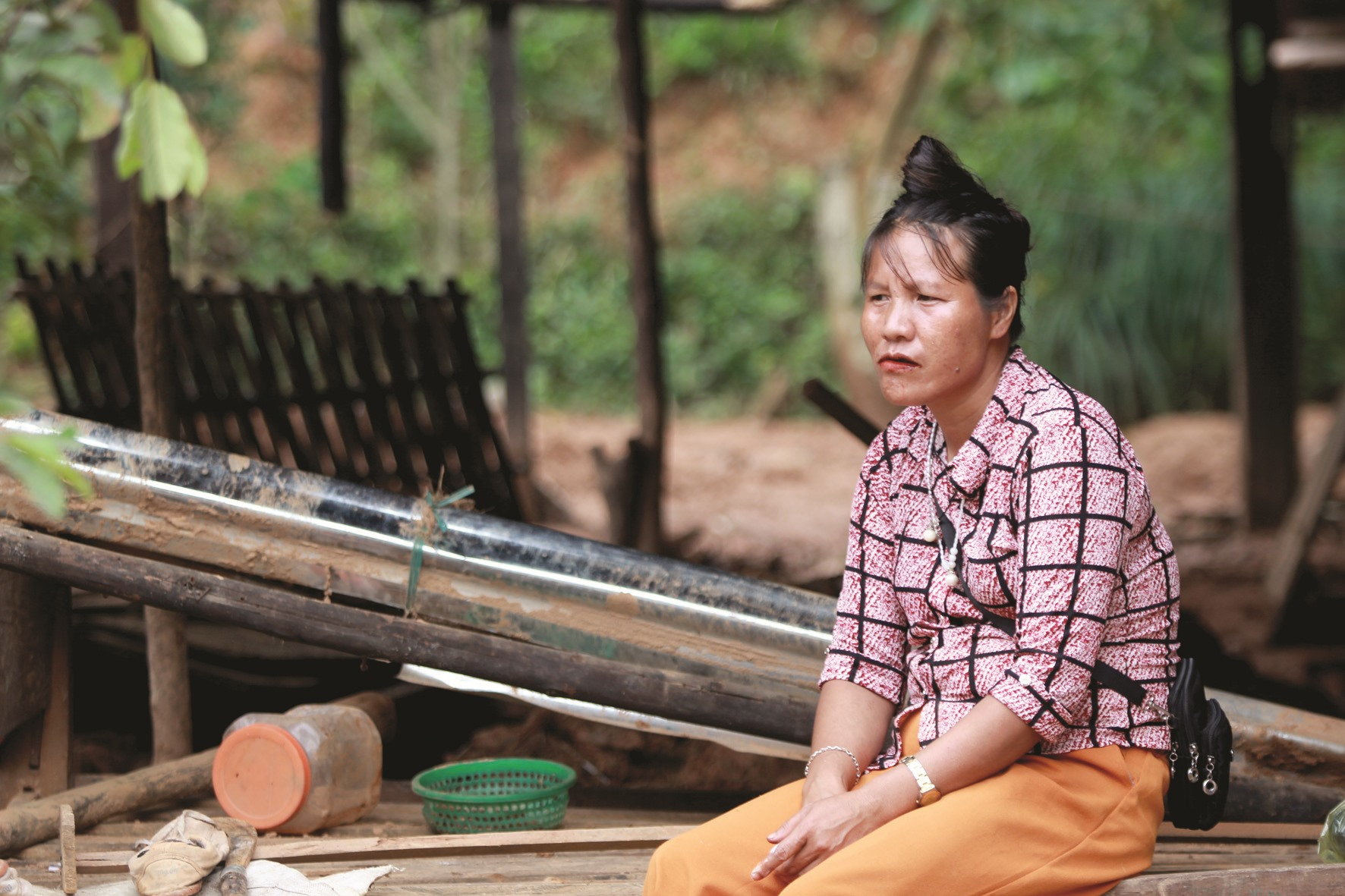 Bà Hồ Thị Dách ngồi trầm ngâm bên căn nhà của mình. Lũ quét gây thiệt hại nặng cho cả làng Triên.