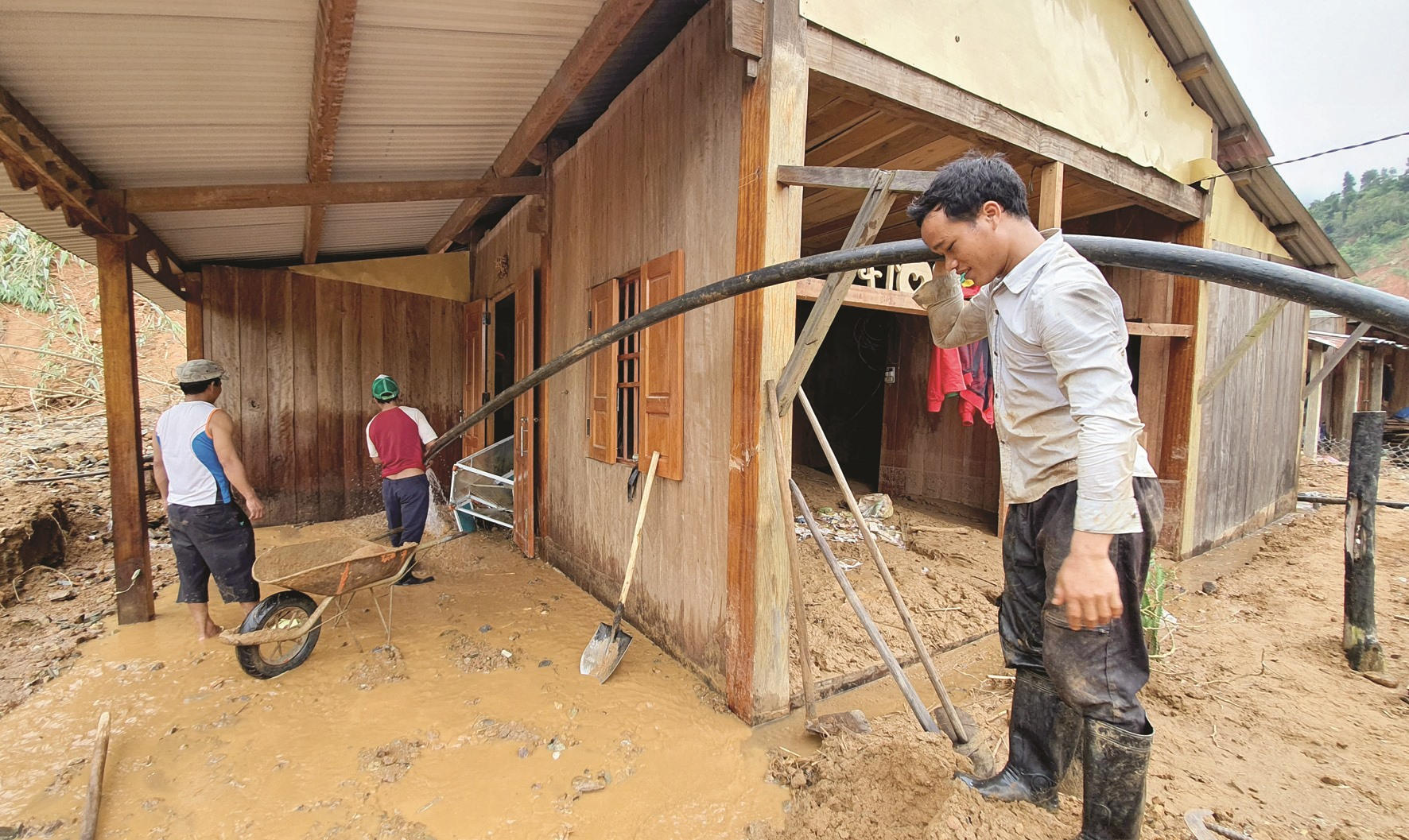 Hồ Văn Êm vác ống nước lớn dẫn từ khe suối về để dội bớt lớp bùn dày lấp kín căn nhà gỗ của mình tại làng Triên.