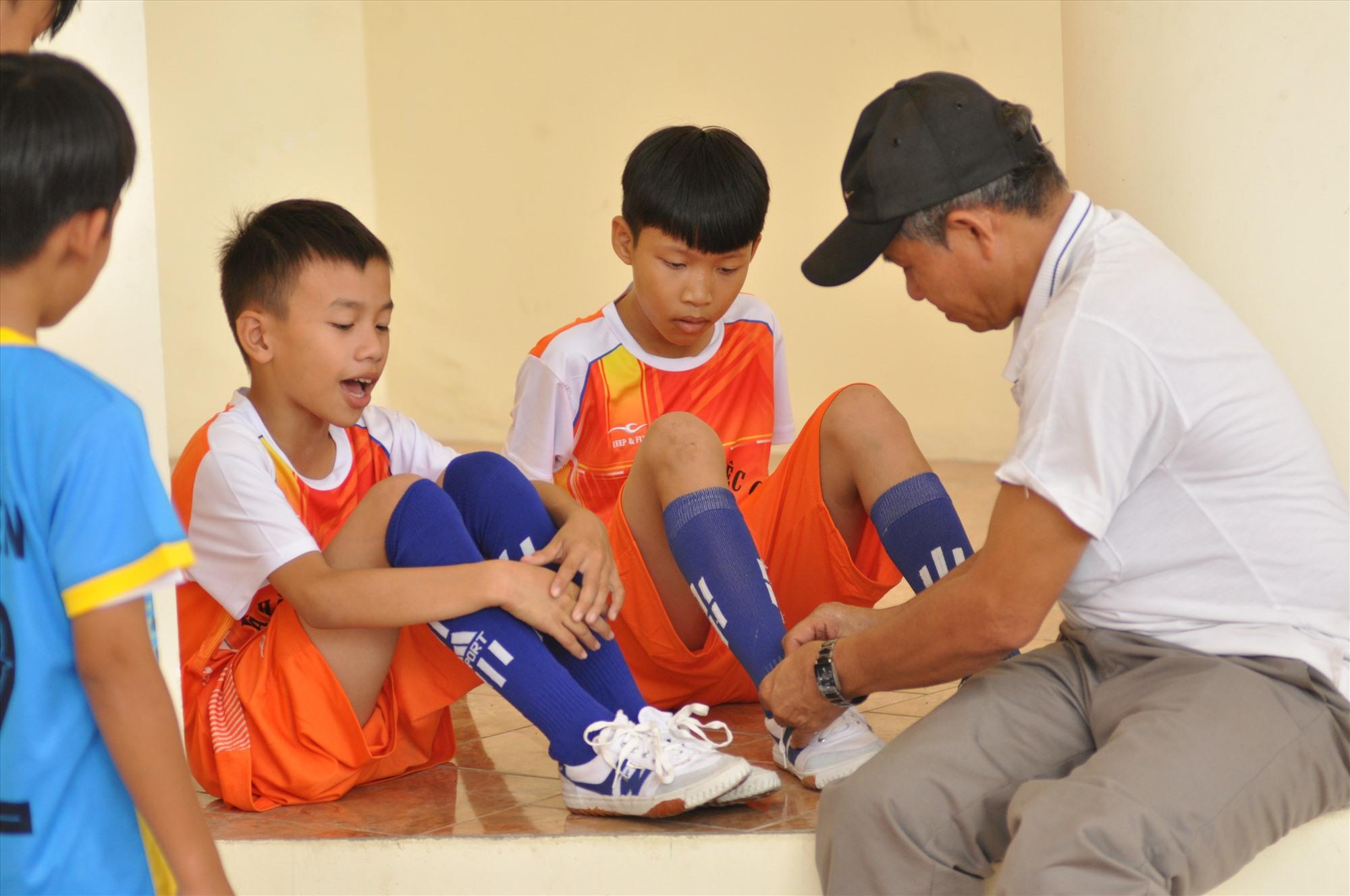 Nhiều cầu thủ nhí ít khi đá bóng bằng giày nên HLV đội bóng Duy Xuyên phải cột dây giày cho các em. Ảnh: X.P