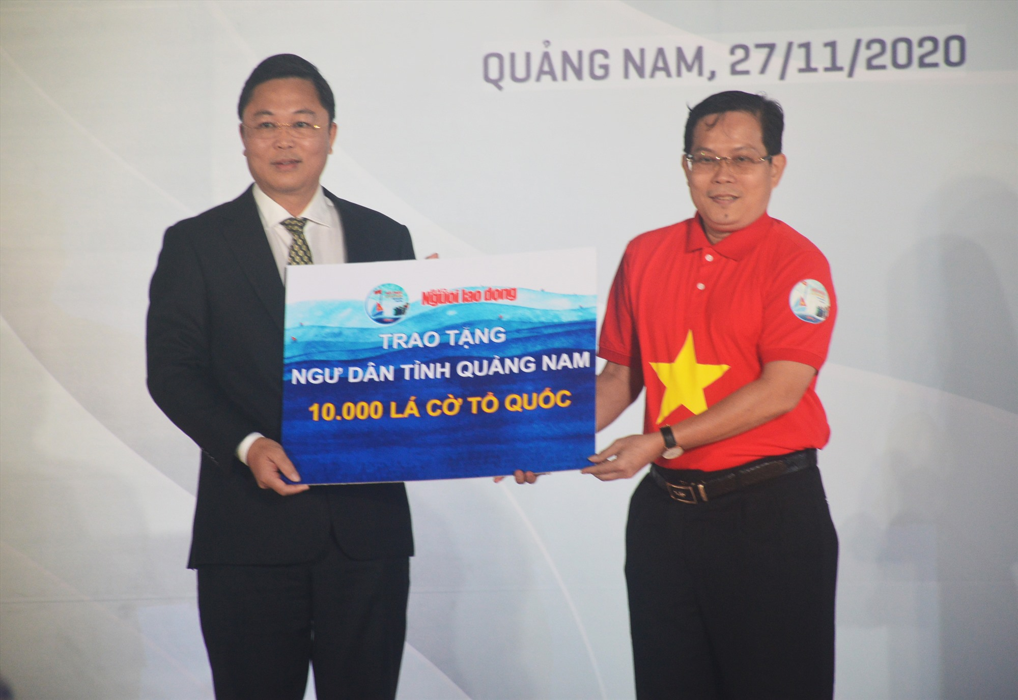 Chủ tịch UBND tỉnh Lê Trí Thanh tiếp nhận 10 nghìn lá cờ tổ quốc từ Báo Người lao động trao tặng động viên ngư dân vươn khơi bám biển. Ảnh: T.L