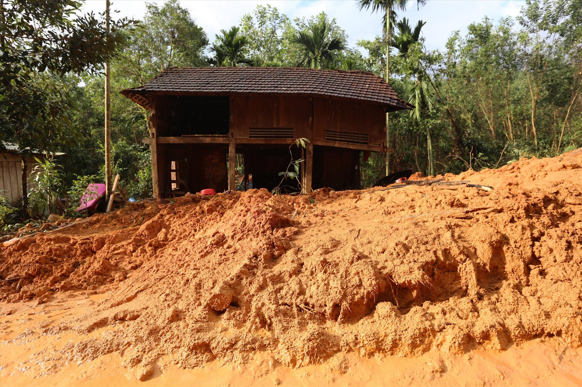 Nhà của bà Hồ Thị Phải, thôn 1, xã Trà Giác, huyện Bắc Trà My nằm ven đường bị đất sạt lở xuống vùi lấp 1 m. Ván thưng xung quanh bị đẩy bung ra khỏi nhà, hôm sạt lở mọi người kịp chạy thoát ra ngoài.