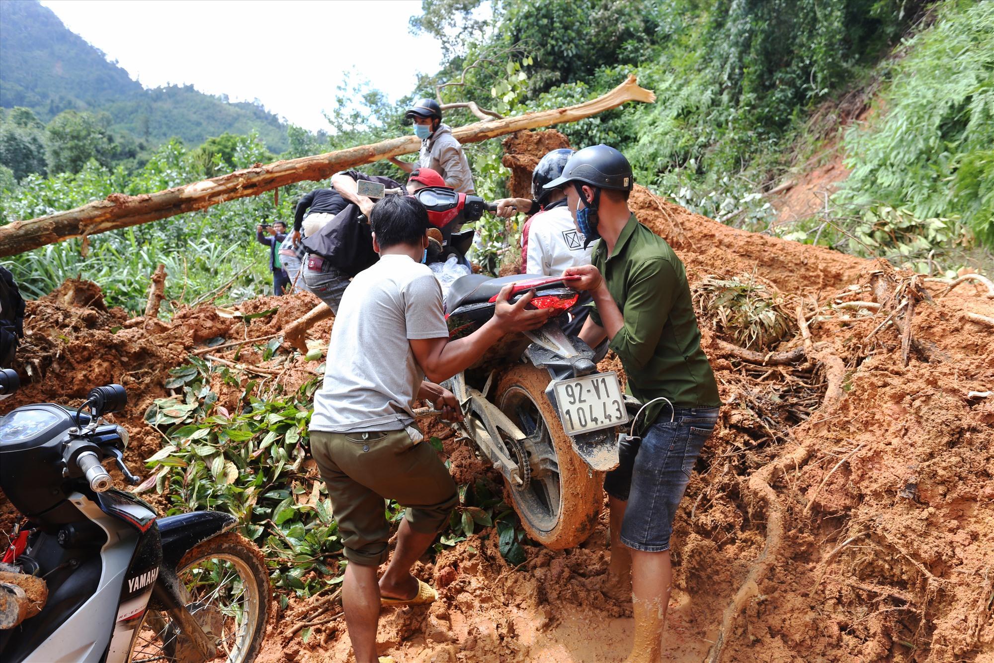 Sau sạt lở chưa khắc phục nên người dân giúp nhau đưa xe máy đi qua đoạn xã Trà Giác, sáng 29/10.